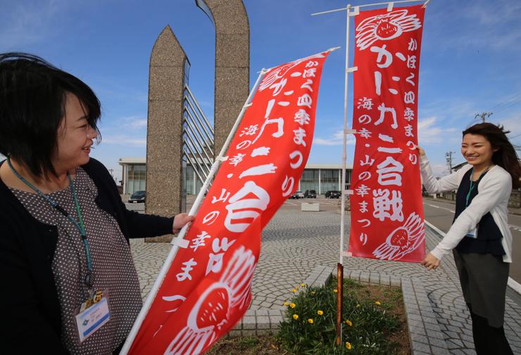 イベントをPRするのぼり旗を掲げる市職員=かほく市七塚生涯学習センター駐車場