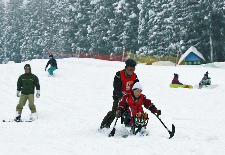 県などが2012年に開いた障害者スキーの体験教室。椅子に座って滑るチェアスキーなどを楽しんだ=新発田市