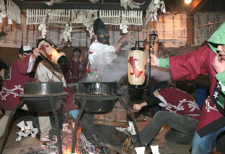 釜の湯を素手で豪快にはじく「湯切り」=1日午後10時8分、飯田市南信濃の日月神社