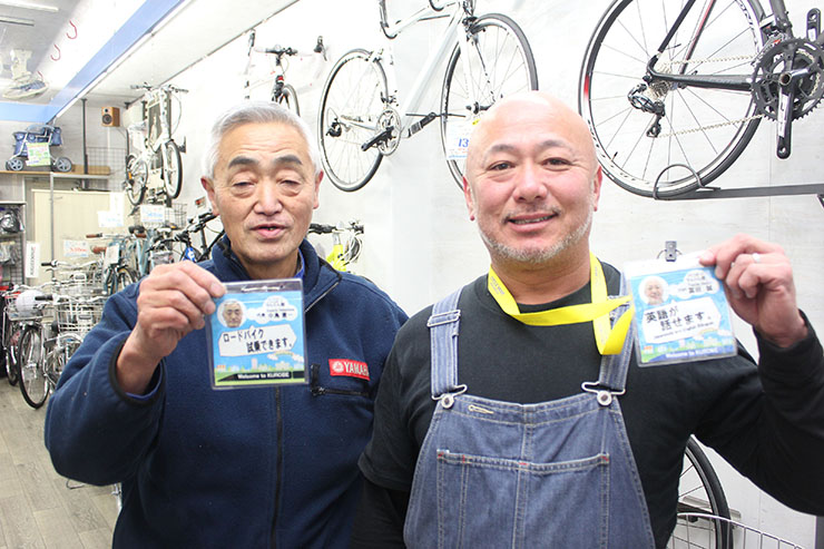 自分ができることを紹介したウェルカム名札を見せる自転車店のスタッフ