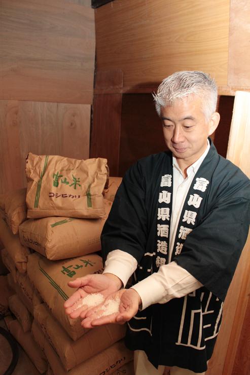 精米した舟橋村産のコシヒカリを手にする桝田社長