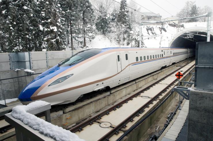 JR東日本、西日本による車両走行試験が始まり、雪景色の中を新幹線飯山駅から上越妙高方面(奥)へと向かうE7系=8日午前10時3分、飯山市
