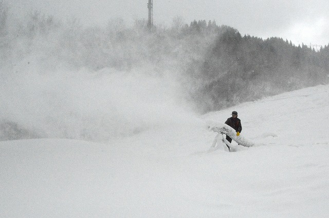20日のオープンに向け稼働を始めた人工造雪機。斜面は自然雪ですでにうっすら白くなっている=5日、南越前町の今庄365スキー場