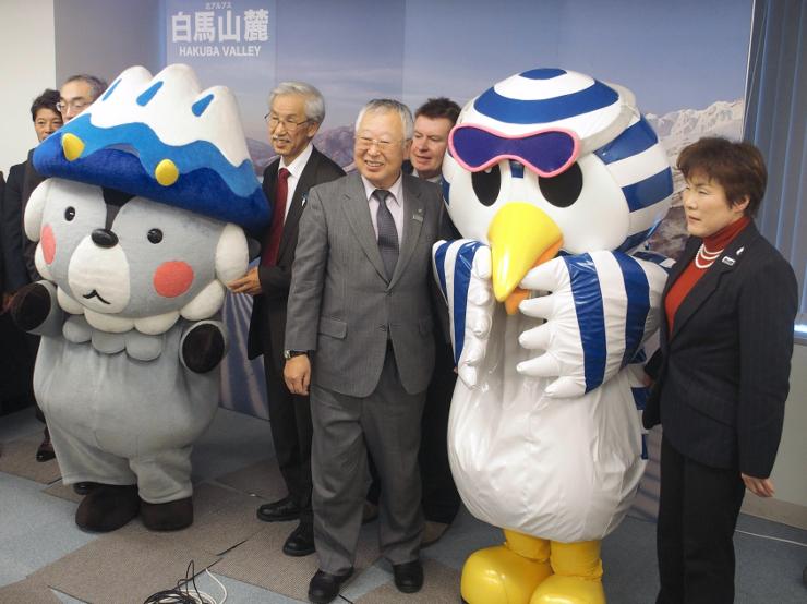 マスコットキャラクターとスキー場が開業したことをアピールする松本久志小谷村長(前列中央)ら=8日、都内