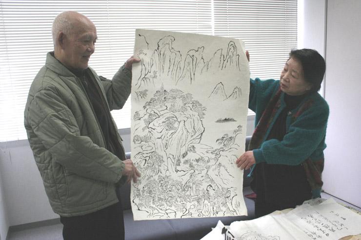 手掛けている山水図を手にする小野さん(左)と妻陽子さん=北國新聞社七尾支社