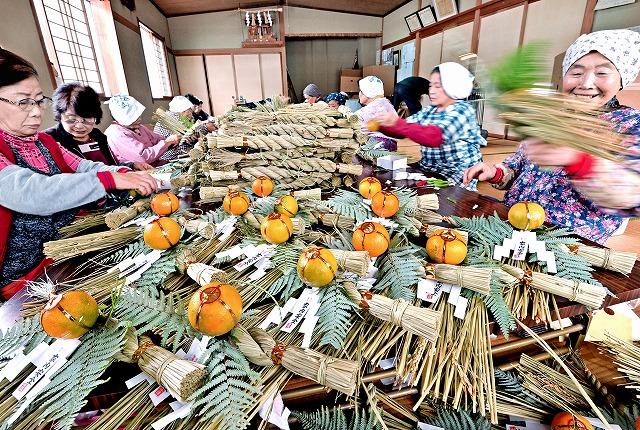 手作業でしめ縄飾りを仕上げる地元の女性たち=10日、池田町水海
