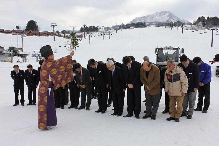雪が降り積もったゲレンデで今季の安全を祈るスキー場の関係者=10日、上越市安塚区須川