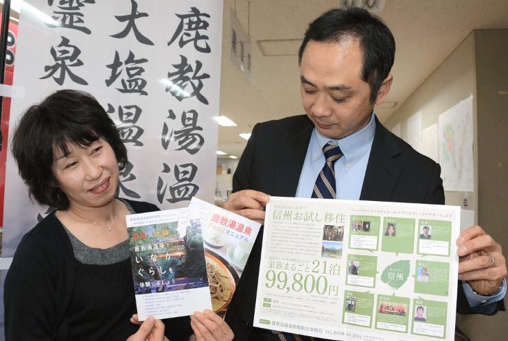 「信州お試し移住」プランのチラシや冊子を持つ斎藤さん(右)ら