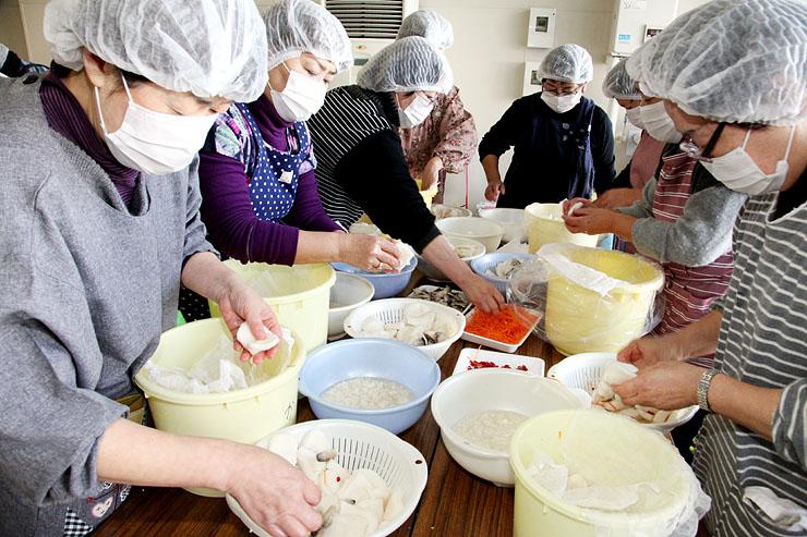 カブに塩サバを挟んでたるに漬け、かぶらずしを作る参加者=JAなんと愛菜ふれあい館