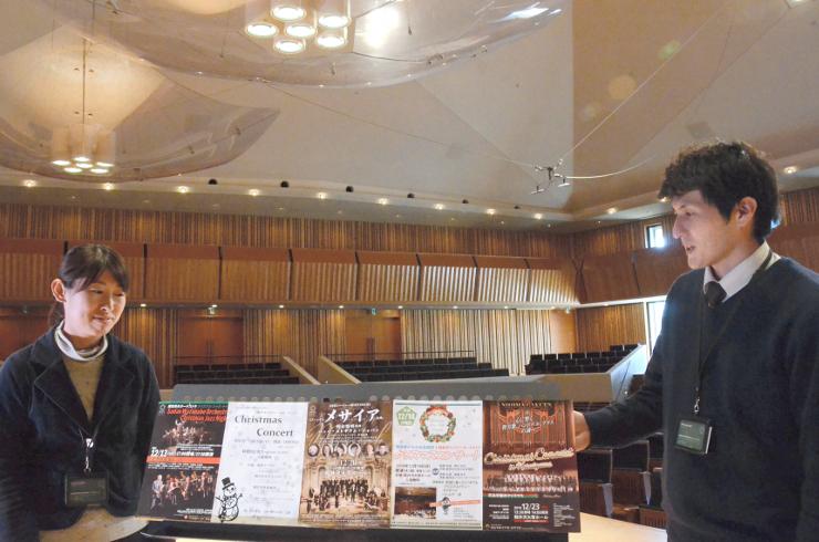 軽井沢大賀ホールで開かれる五つのクリスマス公演のチラシをホールのステージで紹介するスタッフ