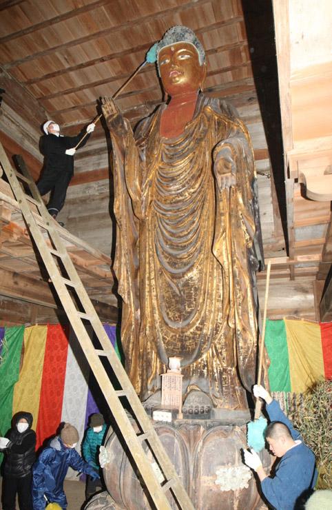 仏像にたまったほこりを落とす僧侶や檀信徒=15日午前10時半、羽咋市滝谷町の妙成寺