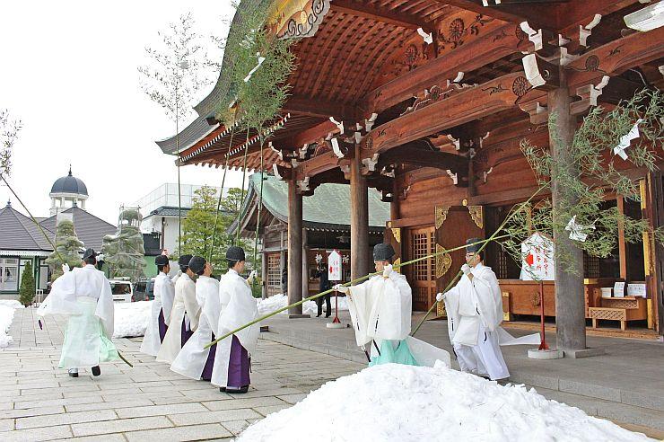 長いササを使い、護国神社の社殿を清める神職(16日午前、新潟市中央区)