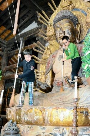 木造釈迦如来坐像のほこりを落とす団員=21日、福井県小浜市国分の国分寺