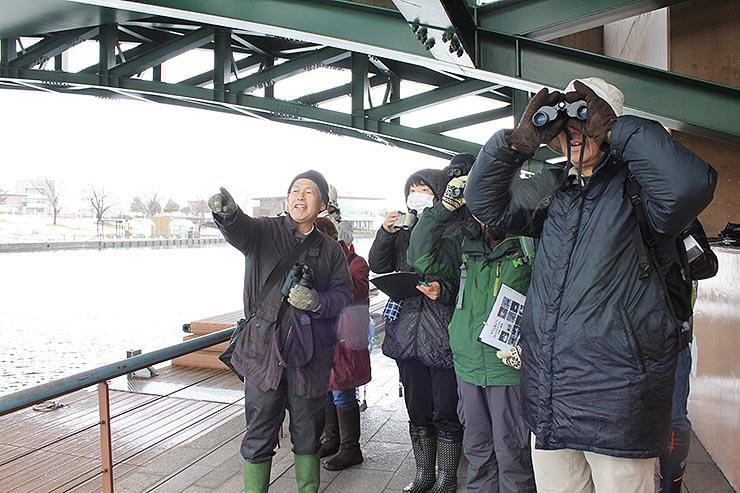 大住さん(左)の解説を聞きながら、水鳥を観察する参加者