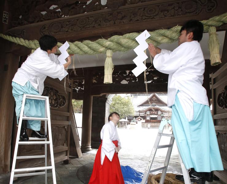 しめ縄を取り換える神職と巫女=22日午前9時40分、金沢市の尾山神社
