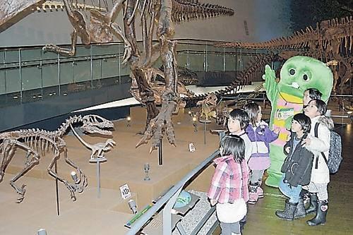 一日館長を務め、子どもたちと館内を見て回るガチャピン=23日、勝山市の県立恐竜博物館
