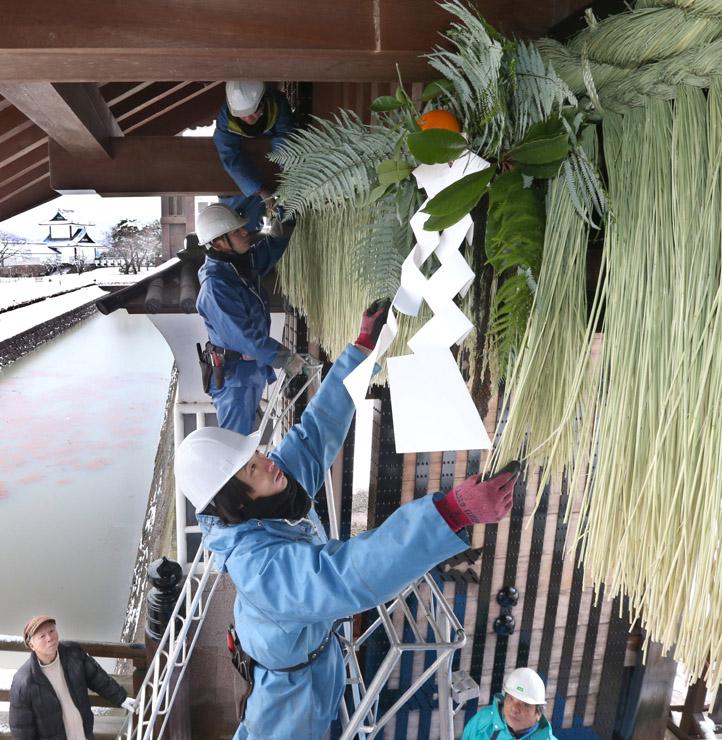 藩政期の様式を再現したしめ飾りを取り付ける担当者=26日午前10時半、金沢城公園