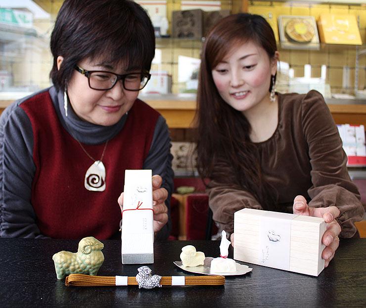 スズの皿に乗った羊の形のホワイトチョコを見る中島社長(左)と大野さん。手前は同じ形の帯留め