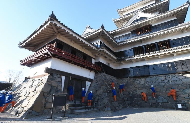 柄の長い竹ぼうきを使い松本城の1年の汚れを落とす職員ら=28日午前9時、松本市