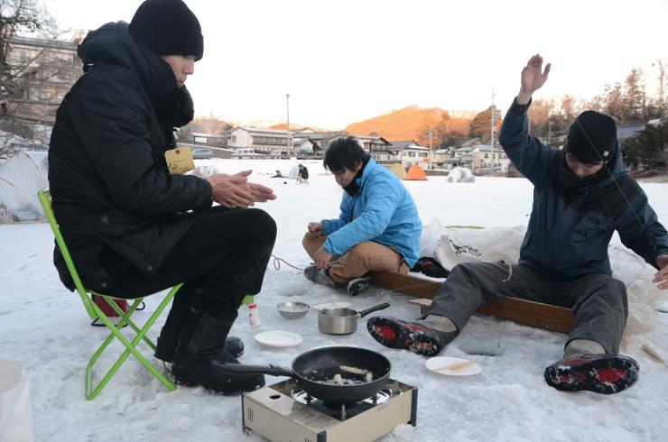 氷上でワカサギを釣る人たち。釣ったその場で天ぷらにして味わった