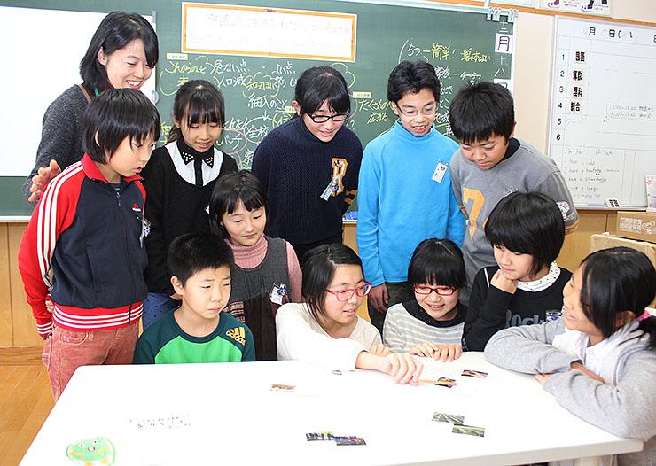 ガイドブック発行に向けて話し合う児童と野村教諭(後列左)