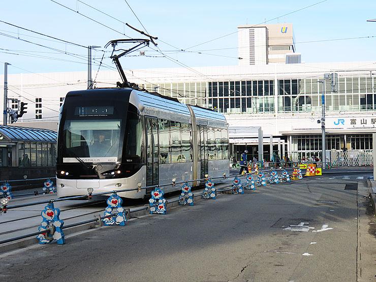 JR富山駅前を走る市内電車環状線「セントラム」。後方では市電が富山駅高架下へ乗り入れるための工事が進む=富山市新富町