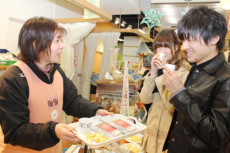 地場もん屋でアップルティーの新茶を来店客に振る舞う下田代表(左)