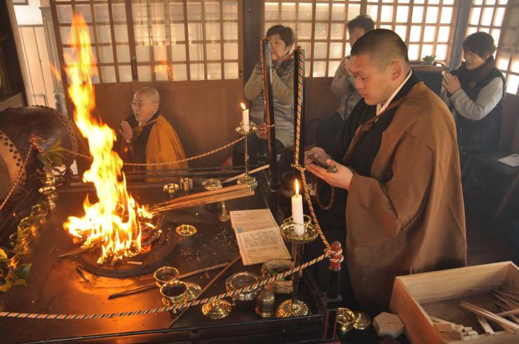 願い事を書いた祈願木を炉にくべると炎が高々と上がった