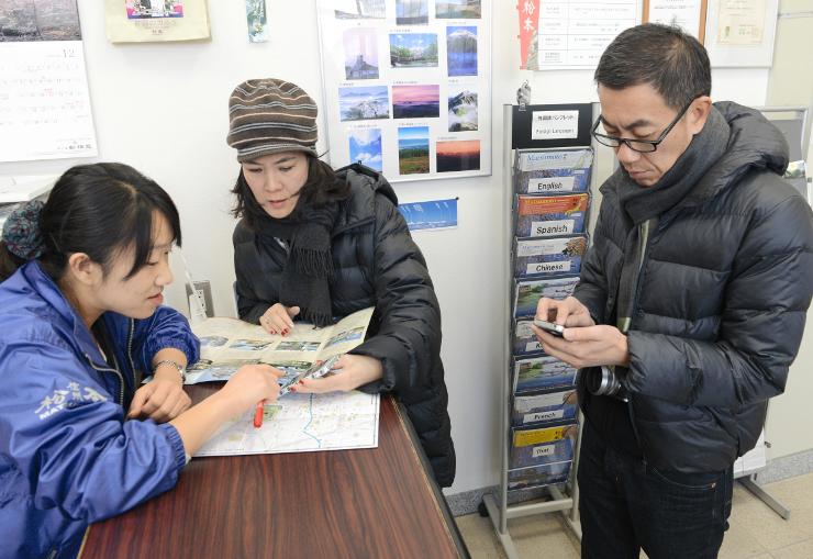 松本駅の観光案内所で無料WiFiの接続を確認するカモルさん(右)