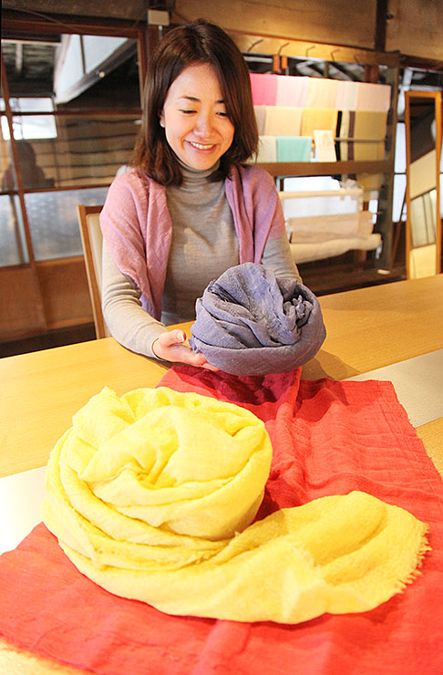 地元産のブルーベリーやシクラメン、ユズで染めた絹ストールを手にする松井さん