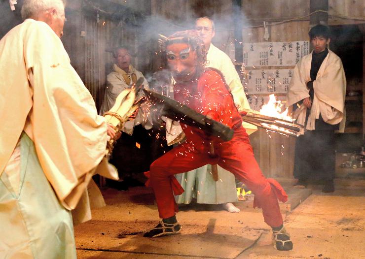 大きなまさかりでたいまつを切りつけ火の粉を散らす赤鬼=5日午前6時48分、天龍村坂部の大森山諏訪神社