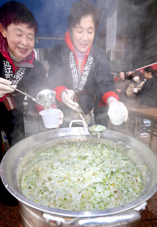 熱々の七草がゆを振る舞う女性職員=6日午前10時45分、金沢市の近江町市場