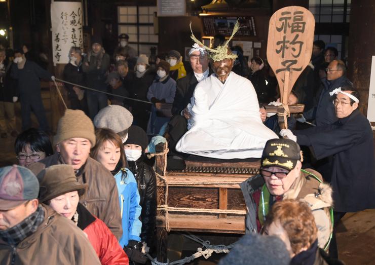 参拝者たちに本堂内を引き回される「びんずる尊者」=6日午後7時20分、長野市の善光寺