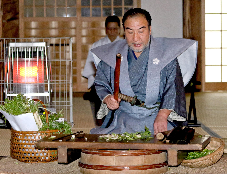 台所道具で七草を刻む大友さん=7日午前7時半、金沢市の尾山神社