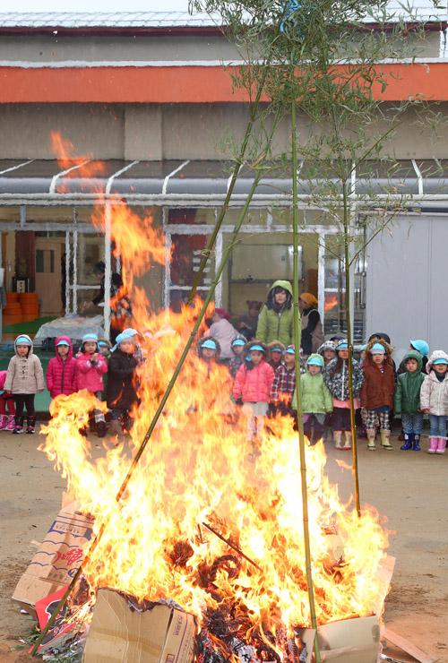 正月飾りを燃やし、無病息災を祈る園児=9日午前10時15分、金沢市粟崎1丁目の粟崎保育園