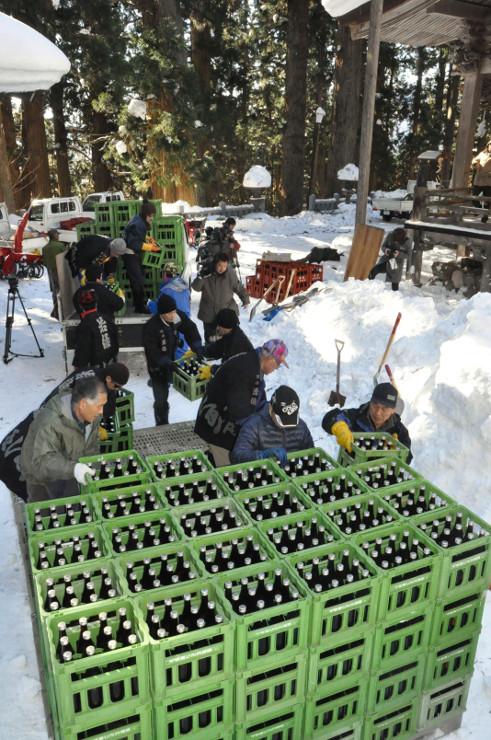 日本酒を雪の中に埋める「蔵納め」の作業をする観光関係者ら