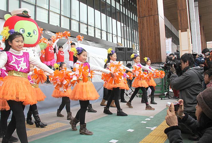 駅長姿のアルクマと一緒に、ステージで「信濃の国」を踊る子どもたち=長野市のJR長野駅