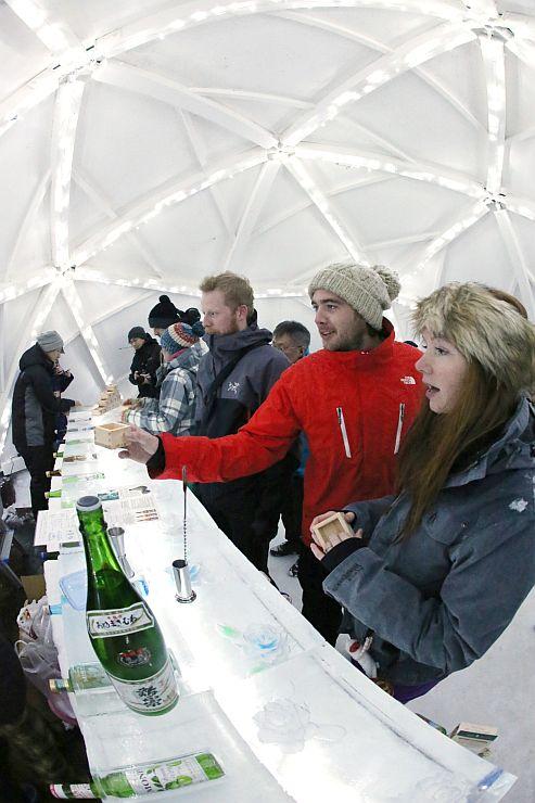 巨大かまくらの中で地酒を味わう外国人観光客=10日、妙高市