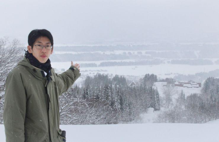 いくつもの階段状になっている河岸段丘を案内する佐藤信之さん。雪の下には広大な農地が広がっている=津南町