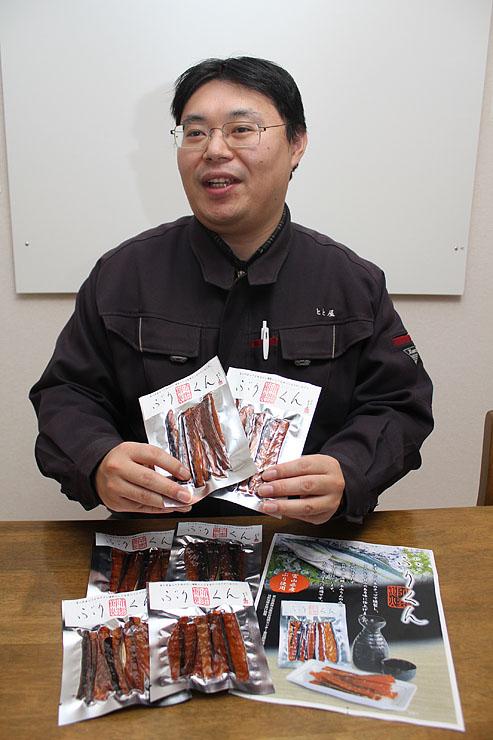 開発した薫製を手に「新幹線で富山を訪れる人に味わってもらいたい」と話す坂井さん