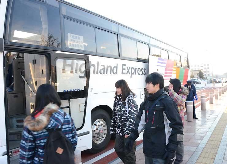 松本駅アルプス口から無料シャトルバスに乗り込むスキー客=11日午前8時すぎ
