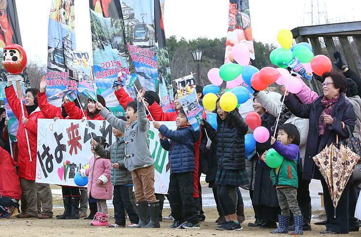 手作りの看板や風船を手にW7系を歓迎する富山商工会議所の役職員ら=富山市の稲荷公園