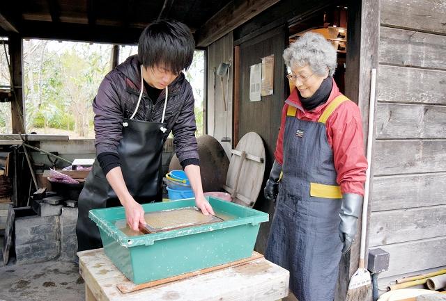 西村さん(右)の指導で竹紙漉きに挑戦。水は冷たかったが、慎重にすくい上げた=おおい町岡田の若州一滴文庫