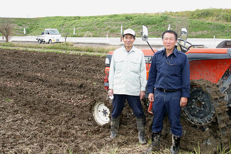増山城跡近くの畑で球根の植え込みに取り組む田中さん(左)と信田さん=昨年11月、砺波市増山