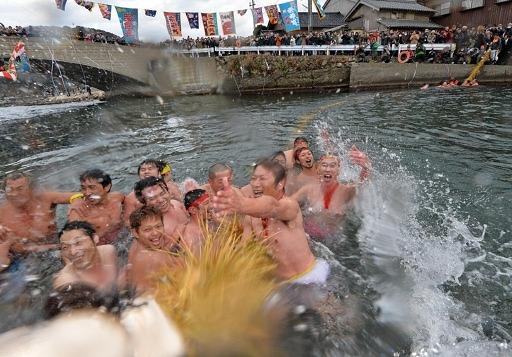 身を切るような冷たい水の中で威勢良く綱を引き合う男衆=18日、美浜町日向