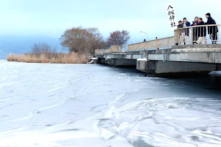 諏訪湖の様子を見る八剣神社関係者ら。湖岸近くは氷が張っているが、沖ではボートが走ったり水鳥が泳いだりしていた=20日、諏訪市豊田