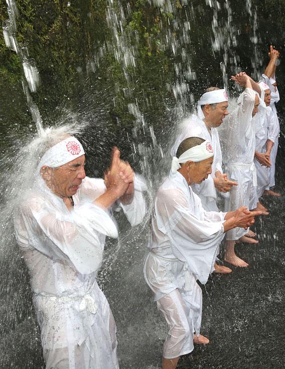 気合を入れ、冷たい滝に打たれる信者たち=大岩山日石寺