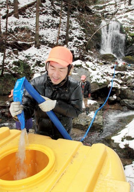 「亀が淵の滝」(右奥)から取水するメンバーたち=18日、福井県小浜市小屋