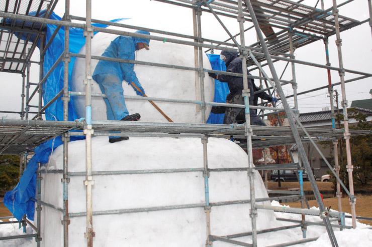 巨大な雪だるまを作る関係者=加賀市片山津温泉