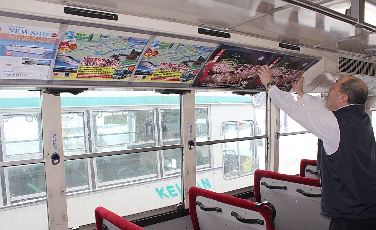 バスの車内に張られた北陸新幹線沿線のイベントなどをPRするポスター=22日、妙高市田口